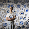 Julie Green, art professor from Oregon State University, poses with with her artwork at The Arts Center in Corvallis, OR. Green has been working on this project for more than 18 years, painting the last meals of U.S. death row inmates. Green intends to paint 50 plates annually until the death penalty is abolished.